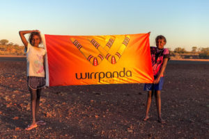 2 female children stand with wirrpanda foundation flag in remote mid west town wiluna in