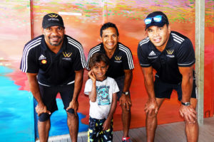 david wirrpanda troy cook and dale kickett of the wirrpanda foundation stand with young male child in front of art mural