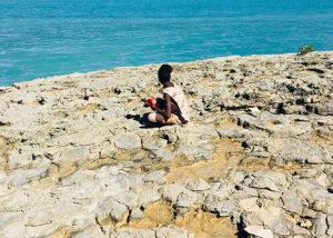 young male from youth justice program sitting on rocks at beach in broome
