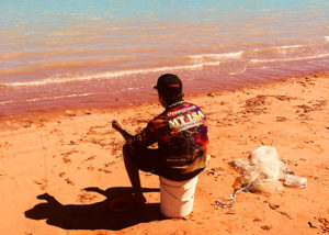 teenage male from youth justice program sits on the beach fishing in broome