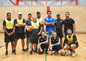 a group of wirrpanda staff and jobseekers playing basketball with brendon ah chee of the west coast eagles