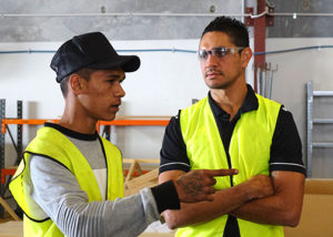 jarrad oakly nicholls with male program participant in high vis and safety glasses pointing