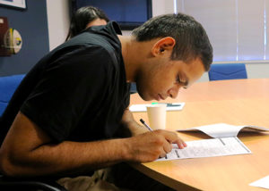 young adult male participant signing employment contract at desk