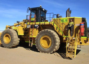young adult male jobseeker in PPE stands on mining truck