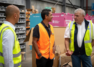 troy cook stands with 2 men from amcap in high vis vests in warehouse