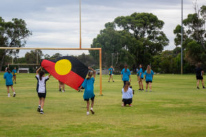 group of deadly sista girlz students playing football on grass oval