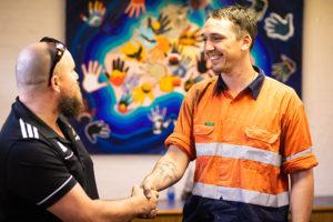 2 men shaking hands and smiling standing in front of aboriginal art