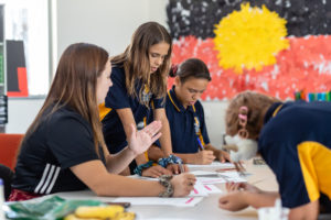a group of deadly sista girlz students working at their desks in front of aboriginal flag