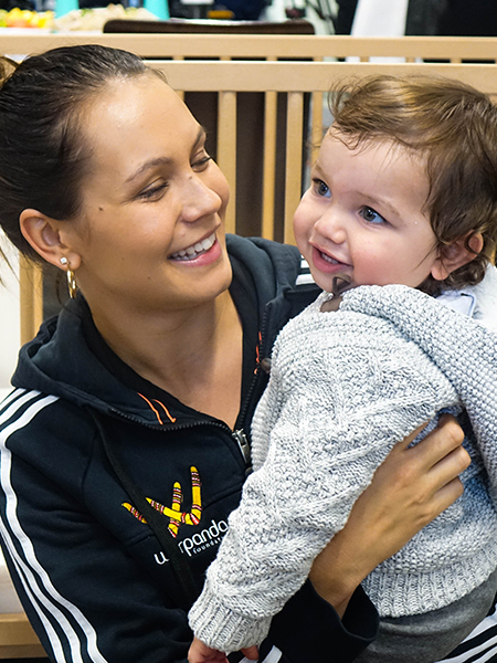 adult female smiling and holding baby