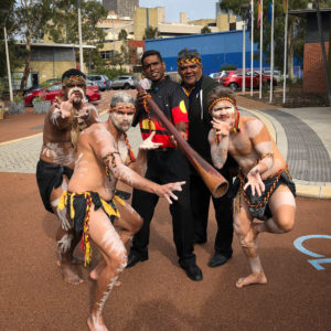 a group of men in aboriginal cultural dress in dance poses
