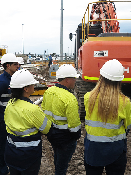 group of people facing away from the camera in hard hats and high vis on a building site