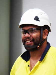 young adult male jobseeker in hard hart and high vis smiling