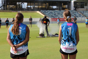 deadly sista girlz students watching an aboriginal smoking ceremony on a cricket ground