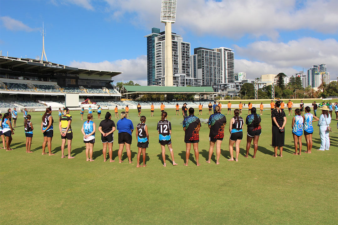 a group of deadly sista girlz students an mentors stand in a circle on a cricket ground with grandstand in the background